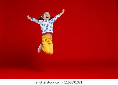 funny child girl jump wearing glasses on a colored background
