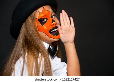 Funny child girl in pumpkin costume for Halloween. Halloween makeup. Face art.