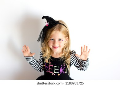 Funny child girl in witch costume for Halloween on a white background. Happy Halloween.