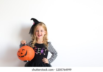 Funny child girl in witch costume for Halloween with pumpkin Jack on a dark background. Happy Halloween.