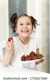 funny child laughs and eats strawberries. spring. April-may.