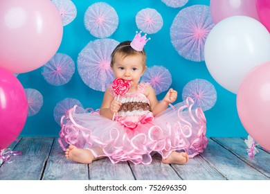 Funny child with a lollipop in the shape of a heart, happy little girl with a crown on her head eating a large sugar lollipop, isolated on a bright blue background with pink balls, studio