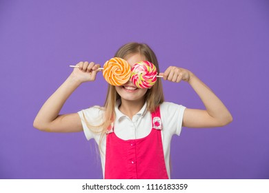 Funny child with lollipops on violet background. Girl smiling with candy eyes. Little kid smile with candies on sticks. Sweet look. Candyshop concept. Childhood and happiness. Having fun with candies.