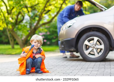 Funny child in orange safety vest during his father repairing family car on background. Vehicle breakdown on travel trip.