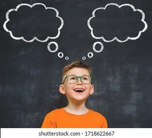 Funny child in orange shirt dreams. Dream clouds drawn on blackboard.