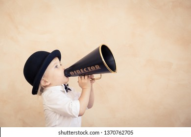Funny child playing at home. Kid shouting through vintage megaphone. Communication and retro cinema concept