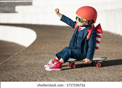 Funny child playing with toy wings. Happy kid having fun outdoor. Childhood dream and imagination concept