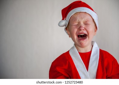 Funny child in Santa Claus costume is crying without Christmas present. Tradition of family holidays.
