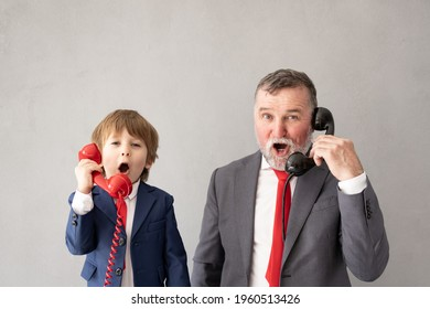 Funny child and senior man pretend to be businessmen. Grandfather and kid playing at home. Education, start up and business idea concept