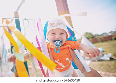 Funny child, the child smiles with a pacifier in his mouth. On the street, in the hands of the mother, among the multicolored ribbons