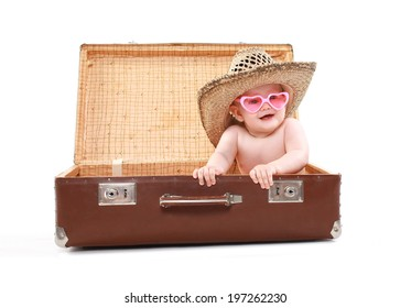 Funny child in sunglasses and summer straw hat looks out of a suitcase, tours, travel, vacation - concept
