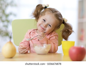 Funny child toddler eating healthy food with a spoon at home