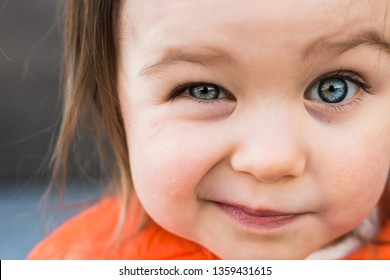 Funny Child Toddler Girl Winking Her Eye. Closeup Portrait, Beautiful Blue Baby Eyes