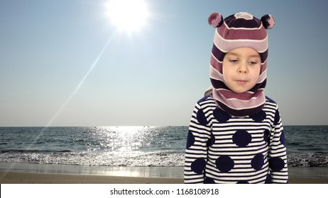 83aeae0bbb2 A funny child in a winter hat is crooked and picks at the nose. A