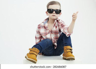 Funny child.fashionable little boy in sunglasses.stylish kid in yellow shoes. fashion children