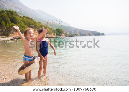 Funny Children Brother And Sister Playing With Stones On The Beach Concept Of Summer