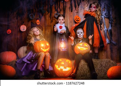 Funny children in carnival costumes on halloween. Halloween party with pumpkins.