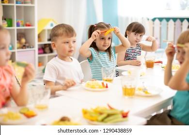 funny children eating vegetables in kindergarten or nursery