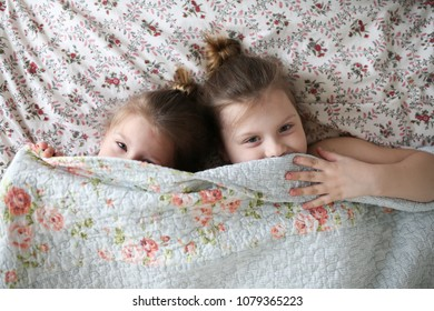 Funny children embrace, play under a blanket on the bed. Concept happy childhood and siblings. Bright real interior and toning.