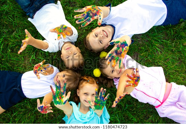 Funny children lie on the grass and show that their hands are painted with colorful paints