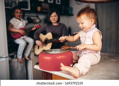 Funny children play music on kitchen tools, loud children make noise in the kitchen, children are quarantined at home