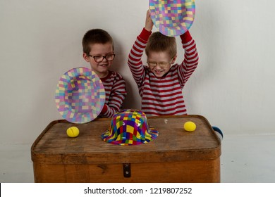 Funny children play scammers. Cute little kid boy in colorful clothes. Fraudulent game of a thimble. 1 april fool day. The shell game (also known as thimblerig, three shells and a pea). Copy space.