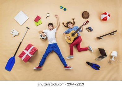 Funny children are playing together. Lying on the floor with guitar and ball