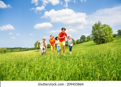 Funny children running together in the field