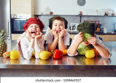 Funny children in the uniform of cooks in the kitchen.