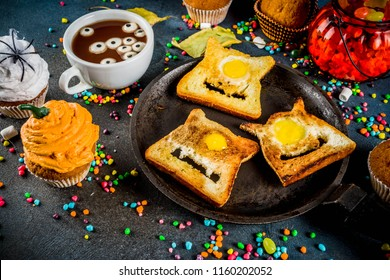 Funny children's treats for Halloween, an idea for a festive breakfast. Sandwiches toast with eggs, looking like creepy monsters, hot chocolate with marshmallow eyes and funny monster cupcakes.
