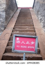 """Funny Chinese sign at Great Wall of China saying """"No More Steps"""" in front of a set of steps."""