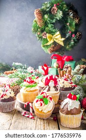 Funny Christmas cupcakes. Homemade sweet cupcakes with sugar glaze in form on christmas decoration and symbols, on wooden background with xmas decor
