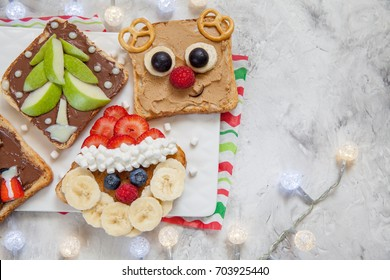 Funny Christmas faces toasts with banana, strawberry and blueberry
