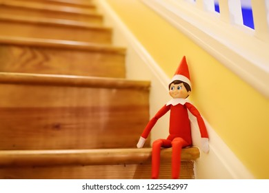 Funny Christmas toy elf on stairs. American christmas traditions. Xmas activities for family with kids.