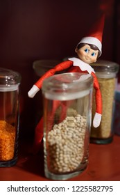 Funny Christmas toy elf on kitchen shelf. American christmas traditions. Xmas activities for family with kids.