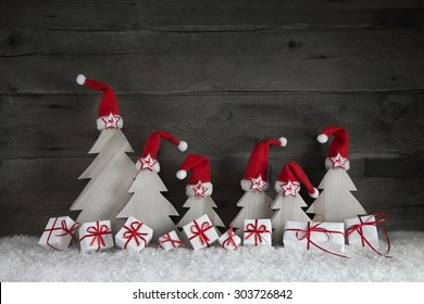 Funny christmas trees with santa hats and gift boxes on wooden background with red ribbon and snow for decoration.