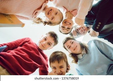 Funny class of schoolchildren and teacher having fun sticking the heads together