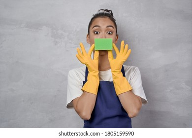 Funny cleaning lady in uniform and rubber gloves playing with kitchen sponge, looking at camera and smiling while standing against grey wall