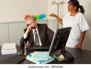Funny cleaning woman cleaning the office of the manager including his face