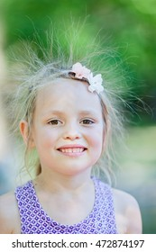 Funny close up portrait of little girl with electrified hair by static electricity, causing by sliding at children playground.