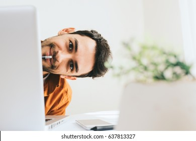 Funny close up shot of happy and smiling young male executive hidden behind laptop at office with pencil on mouth. Young European businessman working at home. Handsome salesman have secret of success