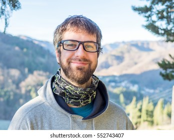 funny close-up portrait of young man with green eyes and brown beard wearing black glasses and gray sweatshirt and with montain on background. Guy looking on camera outdoor
