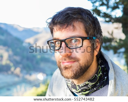 50521d850cec funny close-up portrait of young man with green eyes and brown beard  wearing black glasses and gray sweatshirt and with montain on background.