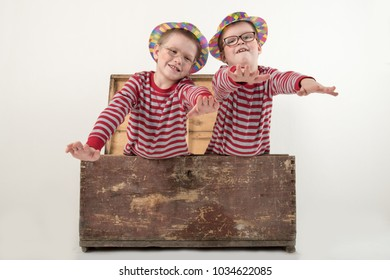 Funny clown children dressed up in costumes and represent the circus. The child is playing at home. The hat is a bowler and a yellow patch on the nose. 1 April. The concept of a fool's day. Copy space