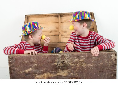 Funny clown children dressed up in costumes and represent the circus. child is playing at home. hat is a bowler and yellow patch on the nose. 1 April. Concept of  fool's day. Copy space.