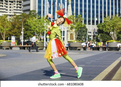 Funny clown in comical concept. Actor shows pantomime against the cityscape.