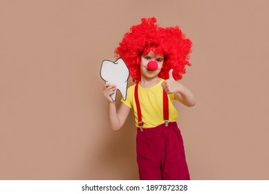 Funny clown girl child in a red wig and with a nose holding a mock-up of a tooth and brush isolated against the background of a Set Sail Champagne flower. Kid teeth hygiene, teeth cleaning concept.
