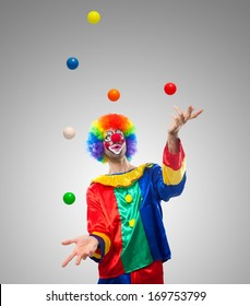 Funny clown juggling many balls
