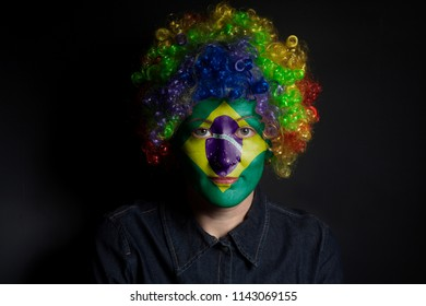 Funny clown woman with painted Brazil Flag isolated on black background