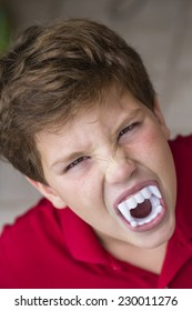Funny color photo with the expression of a nine year old, white, with vampire teeth, scaring, celebrating halloween